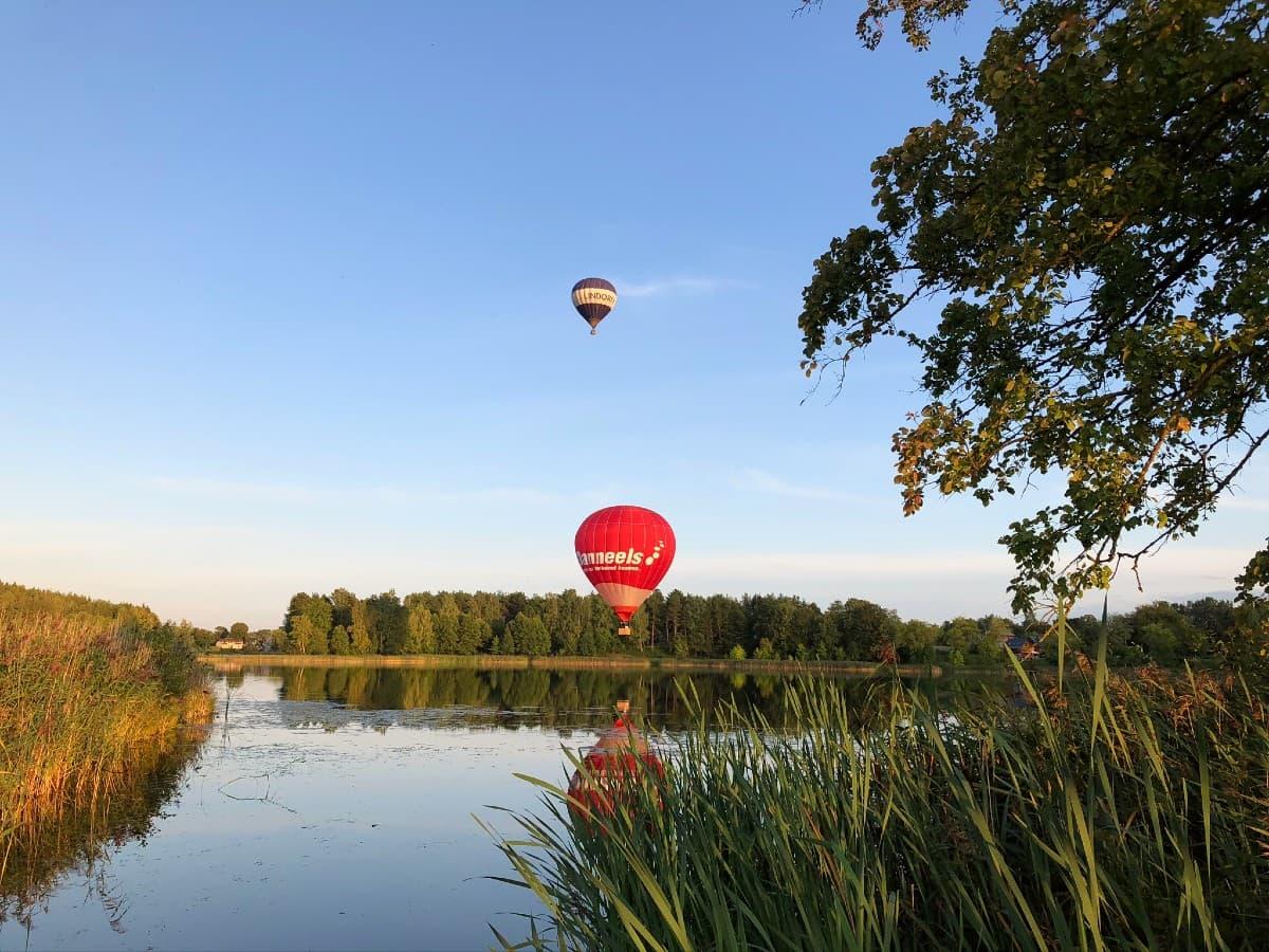 Du oro balionai skrenda virš ežero